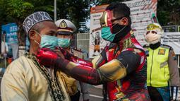 Petugas kepolisian berpakaian superhero memakaikan masker kepada warga di jalan kawasan Pasuruan, Jawa Timur, Kamis (9/4/2020). Hal tersebut bertujuan untuk mengantisipasi penyebaran Virus Corona (COVID-19). (JUNI KRISWANTO / AFP)