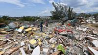 Warga memeriksa puing-puing di mana rumah mereka berdiri sebelum gempa dan tsunami di Petobo, Palu, Kamis (4/10). Wilayah Kelurahan Petobo di Palu menjadi salah satu daerah yang terkena dampak parah karena 'ditelan bumi'. (AFP/ ADEK BERRY)