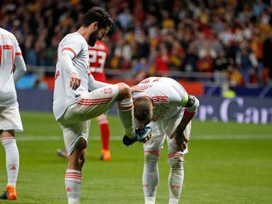 Kapten timnas Spanyol, Sergio Ramos mencium sepatu rekan setimnya Isco Alarcon usai mencetak gol kedua saat pertandingan persahabatan melawan Argentina di stadion Wanda Metropolitano di Madrid (27/3). (AP Photo / Paul White)