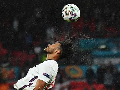 Bek Inggris Tyrone Mings menyundul bola saat pertandingan sepak bola Grup D Euro 2020 antara Inggris melawan Skotlandia di Stadion Wembley, Jumat (18/6/2021). (Foto: AFP/Pool/Justin Tallis)