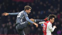 Gelandang Bayern Munchen Thomas Mueller (kiri) menendang kepala bek Ajax Amsterdam Nicolas Tagliafico dalam laga Grup E Liga Champions di Amsterdam, Belanda, Rabu (12/12). Mueller disebut tak sengaja saat insiden itu terjadi. (EMMANUEL DUNAND/AFP)
