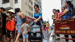 Warga membawa wadah berisi air usai mengisinya dari truk tangki pasokan pemerintah di Hanoi, Vietnam, Kamis (17/10/2019). Warga Hanoi melaporkan bahwa air ledeng yang mereka gunakan bau plastik terbakar. (Nhac NGUYEN/AFP)