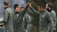 Pemain Juventus, Paulo Dybala dan Alex Sandro saat sesi latihan jelang laga Liga Champions di Vinovo, Italia, Selasa (6/3/2018). Juventus akan berhadapan dengan Tottenham Hotspur. (AFP/Marco Bertorello)