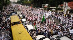 Ribuan Umat muslim  membentangkan spanduk dan mengibarkan bendera saat melakukan aksi menuju Balai Kota Jakarta, Jumat (14/10). Mereka mendesak Gubernur DKI Jakarta, Basuki Tjahaja Purnama mundur. (Liputan6.com/Hemi Fithriansyah)