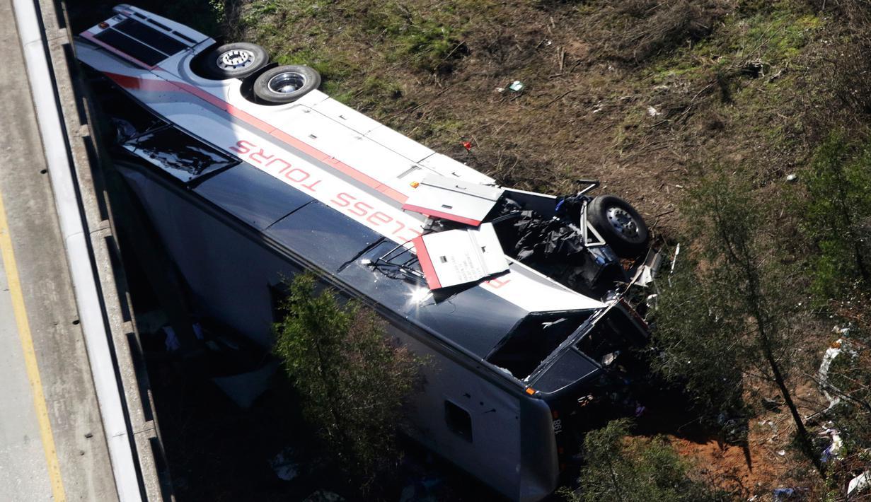 Sebuah bus carteran jatuh usai menabrak pembatas akibat kecelakaan di Loxley, Alabama (13/3). Bus tersebut membawa anggota band SMA di Texas pulang dari Disney World. (AP Photo / Dan Anderson)
