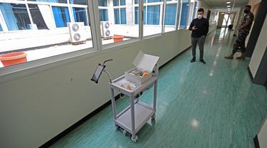 Perancang robot mengendalikan troli robot melalui ponsel di Rumah Sakit Universitas Rafic Hariri di Beirut, 6 Mei 2020. Universitas Lebanon meluncurkan troli robot yang dirancang mahasiswanya untuk membantu dokter dan perawat dalam mengurangi kontak dengan pasien COVID-19. (Xinhua/Bilal Jawich)
