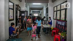 Sejumlah korban banjir berjalan di lorong gedung SDN 01/02 Kampung Melayu, Jakarta, Selasa (9/2/2021). Gedung sekolah di Kebon Pala tersebut menjadi salah satu posko pengungsian bagi sebagian korban banjir Kampung Melayu. (Liputan6.com/Faizal Fanani)