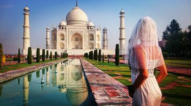 Pavlina Melicharova berfoto menggunakan busana pengantin lamanya di depan masjid ikonik asal India, Taj Mahal. Wanita asal Republik Ceko ini melakukan perjalanan seorang diri berkeliling dunia pasca kegagalan pernikahannya. (facebook.com/TravellingBride)