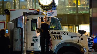 """Penyanyi Lady Gaga berbusana serba hitam dan membawa bendera AS berunjuk rasa di depan Trump Tower, New York City, AS (9/11). Sebagai bentuk protesnya, Gaga mengangkat poster bertuliskan """"Love Trumps Hate.""""( AFP PHOTO/Dominick Reuter)"""