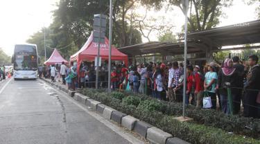 Warga antre untuk menaiki bus tingkat wisata keliling Ibu Kota di kawasan Monas, Jakarta, Sabtu (16/6). Libur Hari Raya Idul Fitri dimanfaatkan oleh sebagian masyarakat Jakarta untuk berlibur ketempat wisata bersama keluarga. (Liputan6.com/Arya Manggala)
