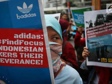 Seorang buruh membawa poster saat melakukan aksi di depan Kedubes Jerman di Jakarta, Selasa (18/7). Dalam aksi itu mereka menuntut Kedubes Jerman untuk membantu menyelesaikan permasalahan yang terjadi pada PT Panarub Dwikarya. (Liputan6.com/Angga Yuniar)