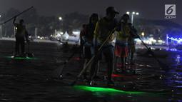 Sejumlah peserta mengikuti night paddling di Ancol, Jakarta, Sabtu (18/5/2019). Indonesia menjadi tuan rumah perhelatan internasional BPJS Ketenagakerjaan Belitong Geopark International SUP (Stand Up Paddleboard) and Kayak Marathon (BGISKM) 2019 di Bangka Belitung. (Liputan6.com/Herman Zakharia)