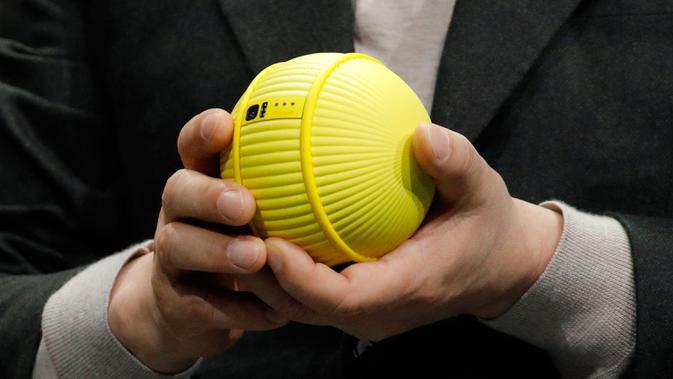 Presiden dan CEO Divisi Elektronik Konsumen Samsung Hyun-Suk Kim memegang robot Ballie saat pameran teknologi CES 2020 di Las Vegas, Amerika Serikat, Senin (6/1/2020). Ballie dibekali kemampuan AI (kecerdasan buatan) dan bahkan bisa jadi 'teman hidup'. (AP Photo/John Locher)