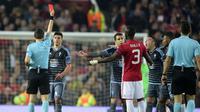 Wasit Ovidiu Hategan memberi kartu merah kepada bek Celta Vigo Facundo Roncaglia dan bek MU, Eric Bailly pada leg kedua Liga Europa di stadion Old Trafford, Inggris,(11/5). Di leg kedua ini MU bermain imbang 1-1 dengan Celta Vigo. (AFP Photo/Miguel Riopa)