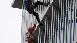 Kepala BNPB Willem Rampangilei (bawah) dievakuasi menggunakan tali dari lantai 10 saat simulasi bencana di Gedung Graha BNPB, Jakarta, Kamis (26/4). Simulai penanggulangan bencana dilaksanakan serentak di seluruh Indonesia. (Liputan6.com/Arya Manggala)
