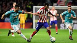 Gelandang Atletico Madrid, Thomas Lemar, berusaha melewati bek Osasuna, Oier Sanjurjo, pada laga La Liga di Stadion Wanda Metropolitano, Madrid, Sabtu (14/12). Atletico menang 2-0 atas Osasuna. (AFP/Cristina Quicler)