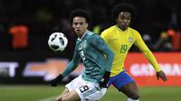 Gelandang Brasil, Willian, berebut bola dengan gelandang Jerman, Leroy Sane, pada laga persahabatan di Stadion Olympiastadion, Berlin, Selasa (27/3/2018). Jerman takluk 0-1 dari Brasil. (AP/Michael Sohn)