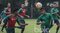 Gelandang Timnas Indonesia U-22, Miftahul Hamdi, membuang bola dari kejaran Saddil Ramdani. Dalam latihan ini pelatih asal Spanyol tersebut terus berupaya mengasah kerja sama dari Garuda Muda. (Bola.com/Vitalis Yogi Trisna)