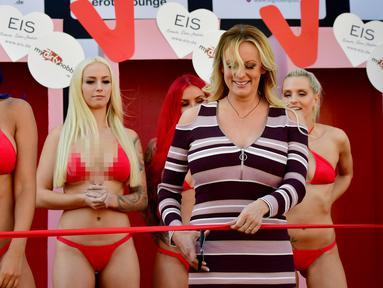 """Bintang porno Stormy Daniels mengunting pita saat membuka Berlin erotic fair """"Venus"""" di Berlin, Jerman (11/10). Stormy Daniels mengklaim pernah berselingkuh dengan Presiden AS, Donald Trump. (AFP Photo/Tobias Schwarz)"""