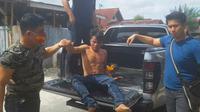Tersangka pembunuh anak tiri setelah ditembak personel Polresta Pekanbaru. (Liputan6.com/M Syukur)