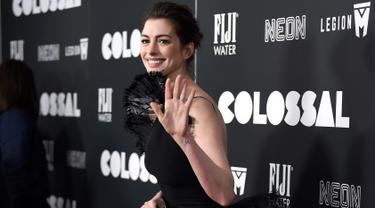 Aktris Anne Hathaway melambaikan tangan ke arah fotografer di karpet merah premiere film 'Colossal', New York City, AS, Selasa (28/3). Aktris pemenang Oscar itu tampil dalam balutan gaun hitam vintage Armani Prive. (Photo by Evan Agostini/Invision/AP)