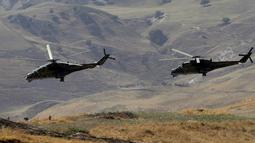 Helikopter militer melintas selama komando strategis dan staf melakukan latihan Center-2019 di lapangan tembak Lyaur, Tajikistan, Rabu (18/9/2019). Prajurit Rusia, Kazakhstan, Kirgistan, Tajikistan, Uzbekistan, India, Pakistan, dan China ikut serta dalam latihan ini. (AP Photo/Grits Sergei)