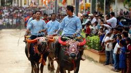Sejumlah peserta menunggangi kerbau ketika mengikuti balapan dalam Festival Pchum Ben di provinsi Kandal, Kamboja, Rabu (20/9). Lazimnya, Pchum Ben digelar di area percandian atau pagoda, juga kawasan permukiman. (AP Photo/Heng Sinith)