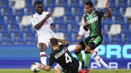 Pemain AC Milan Franck Kessie (kiri) dan pemain Sassuolo Rogerio (kanan) berebut bola pada pertandingan Serie A Italia di Stadion Mapei, Reggio Emilia, Italia, Selasa (21/7/2020). AC Milan menang 2-1 sekaligus menggeser posisi AS Roma dari posisi lima klasemen. (Spada/LaPresse via AP)