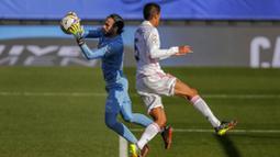 Bek Real Madrid, Raphael Varane, berebut bola dengan kiper Valencia, Jaume Domenech, pada laga Liga Spanyol di Stadion Alfredo Di Stefano, Minggu (14/2/2021). Real Madrid menang dengan skor 2-0. (AP/Manu Fernandez)