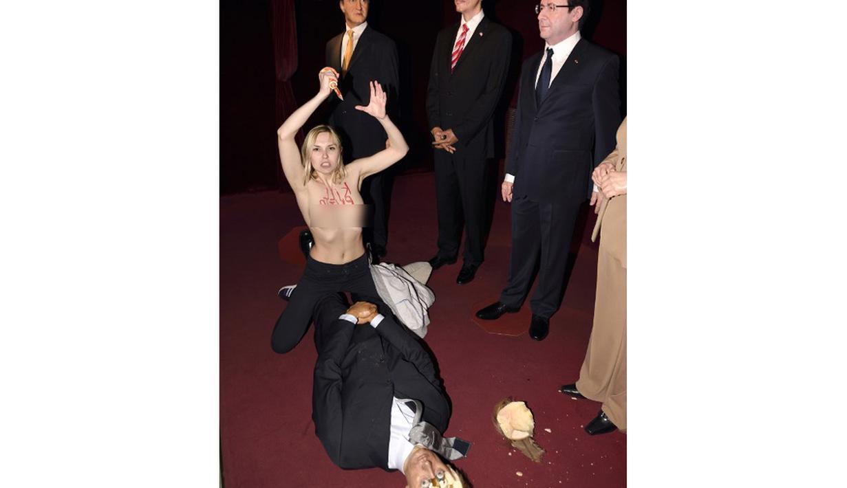 Seorang aktivis Femen menyerang patung lilin Presiden Rusia Vladimir Putin di Museum Grevin, Paris, Kamis (5/6/14). (AFP PHOTO/Eric Feferberg)
