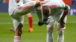 Ekspresi pemain Spanyol, Isco Alarcon saat sepatunya dicium oleh Sergio Ramos usai ia mencetak gol saat pertandingan persahabatan melawan Argentina di stadion Wanda Metropolitano di Madrid (27/3). Isco berhasil mencetak tiga gol. (AP Photo / Paul White)
