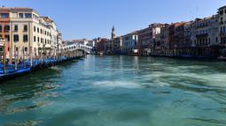Pandangan umum menunjukkan perairan yang lebih jernih Grand Canal di dekat Jembatan Rialto di Venesia pada 18 Maret 2020, . Sejak Italia memberlakukan lockdown akibat pandemi virus corona, air di Kanal Venesia yang biasanya keruh dan gelap berubah menjadi jernih. (ANDREA PATTARO / AFP)