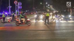 Petugas Kepolisian mengatur pengalihan arus lalu lintas di sekitar perempatan jalan Imam Bonjol dekat Gedung KPU RI, Jakarta, Senin (20/5/2019). Jelang penetapan Presiden dan Wakil Presiden terpilih pada Pemilu 2019, jalan Imam Bonjol di sterilkan hingga 25 Mei. (Liputan6.com/Helmi Fithriansyah)