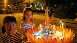 Anak-anak membawa sebuah lentera air untuk dihanyutkan dalam Festival Loy Krathong di Bandar Seri Begawan, Brunei (31/10/2020).  Sekitar 250 orang termasuk sejumlah warga Thailand yang tinggal di Brunei menghanyutkan lentera air untuk perdamaian dan keberuntungan. (Xinhua/Jeffrey Wong)