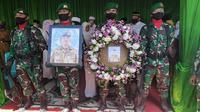 Prajurit TNI memegang foto dan karangan bunga di depan peti jenazah Pelda Anumerta Rama Wahyudi. (Liputan6.com/M Syukur)