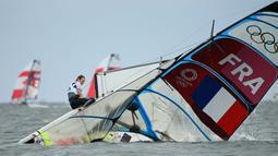 Atlet layar asal Prancis Lili Sebesi dan Albane Dubois menyelamatkan diri diatas perahu layar yang terbalik saat lomba skiff 49er FX 2 layar putri Olimpiade Tokyo 2020 di Enoshima Yacht Harbor di Fujisawa, Jepang, pada 27 Juli 2021. (Foto: AFP/Peter Parks)