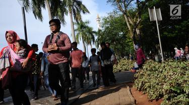 Pengunjung berjalan di kawasan Monumen Nasional, Jakarta, Senin (25/12). Libur perayaan Natal dimanfaatkan warga untuk berwisata di kawasan Monumen Nasional. (Liputan6.com/Helmi Fithriansyah)