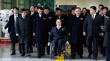 Direktur Komite Paralimpiade Pyeongchang 2018, Lim Chan-kyu (tengah) mengawal delegasi Korea Utara saat mereka tiba di Kantor Transit Korea, dekat Zona Demiliterisasi, Paju, Korea Selatan, Rabu (7/3). (Ahn Young-joon/POOL/AFP)