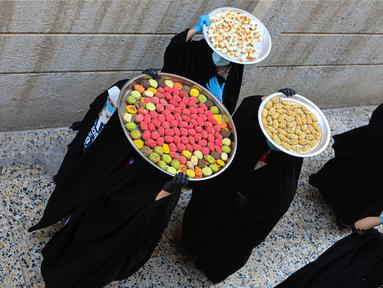 Sejumlah perempuan membawa kue untuk perayaan Idul Fitri yang akan datang di Basra, Irak, Jumat (22/5/2020). Idul Fitri menandai berakhirnya bulan suci Ramadan. (AP Photo/Nabil al-Jurani)