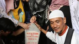 Seorang pria berswafoto dengan latar belakang batu nisan Presiden ketiga BJ Habibie di Taman Makam Pahlawan Nasional Kalibata, Jakarta, Kamis (12/9/2019). Selain berdoa, tidak sedikit juga warga  mengabadikan dengan kamera ponsel. (Liputan6.com/Herman Zakharia)
