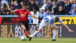 Penyerang Manchester United, Alexis Sanchez, berusaha melewati pemain Huddersfield Town, Erik Durm, pada laga Premier League di Stadion John Smith, Minggu (5/5). Kedua tim bermain imbang 1-1. (AP/Anthony Devlin)
