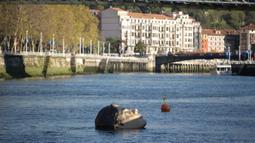 Patung Bihar karya seniman hiperrealis asal Meksiko Ruben Orozco terendam di Sungai Nervion, Kota Bilbao, Basque, Spanyol, 14 Oktober 2021. Patung tersebut merupakan kampanye oleh Yayasan BBK atau badan amal dari pemberi pinjaman Spanyol Kutxabank. (ANDER GILLENEA/AFP)