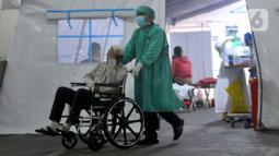 Petugas medis mendorong pasien yang duduk di kursi roda di depan UGD RSUD Cengkareng, Jakarta, Kamis (24/6/2021). Lonjakan kasus virus corona mengakibatkan ruang IGD penuh, pihak rumah sakit lantas mendirikan tenda darurat untuk merawat pasien covid-19. (merdeka.com/Arie Basuki)