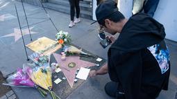 Penggemar mengambil gambar memorabilia yang diletakkan di atas bintang Walk of Fame milik pencipta sekaligus legenda komik-komik Marvel, Stan Lee di Hollywood, California, Senin (12/11). Stan Lee meninggal dunia pada usia 95. (VALERIE MACON / AFP)