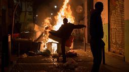 Pengunjuk rasa membakar sampah setelah kematian seorang pedagang kaki lima di distrik Lavapies di Madrid (15/3). Pedagang bernama Mmame Mbage diduga tewas setelah dikejar-kejar aparat kepolisian. (AFP Photo/Olmo Calvo)
