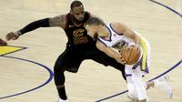 Pemain Cavaliers, LeBron James 9kiri) berusaha menutup pergerakan pemain Warriors, Stephen Curry pada gim pertama final NBA basketball di Oakland, California, (31/5/2018). Warriors menang 124-114. (AP/Marcio Jose Sanchez)