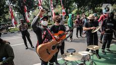 Sejumlah musisi kafe saat melaksanakan aksi di depan Balai Kota Jakarta, Rabu (8/7/2020). Aksi ngamen di depan Balai Kota Jakarta yang diikuti oleh musisi kafe itu untuk menyuarakan aspirasi pekerja seni harian yang terdampak mata pencahariannya selama masa PSBB. (Liputan6.com/Faizal Fanani)