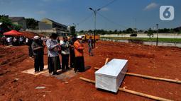 Keluarga korban mensalatkan jenazah untuk dimakamkan di lahan baru tempat pemakaman umum (TPU) khusus COVID-19, Jombang, Tangerang Selatan, Banten,Senin (26/7/2021). Pemkot Tangerang Selatan membuka lahan baru TPU khusus COVID-19 yang dapat menampung 800 makam. (merdeka.com/Arie Basuki)
