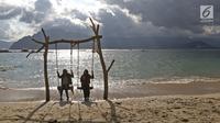 Dua wanita bermain ayunan saat menikmati Pantai Mutiara di Trenggalek, Jawa Timur, Sabtu (7/9/2019). Pantai Mutiara salah satu tujuan wisata yang sedang dikembangkan kabupaten Trenggalek. (Liputan6.com/Herman Zakharia)