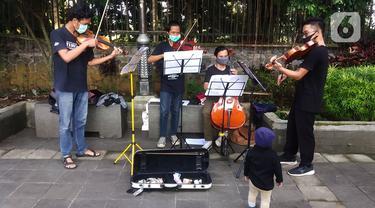 Musisi lokal Bogor memainkan musik klasik di pedestrian Kebun Raya, Jalan Pajajaran, Bogor, Jawa Barat, Minggu (14/6/2020). Untuk memenuhi kebutuhan hidup akibat sepinya job pertunjukan selama pandemi COVID-19, mereka memilih mengamen saat warga berolahraga. (merdeka.com/Arie Basuki)